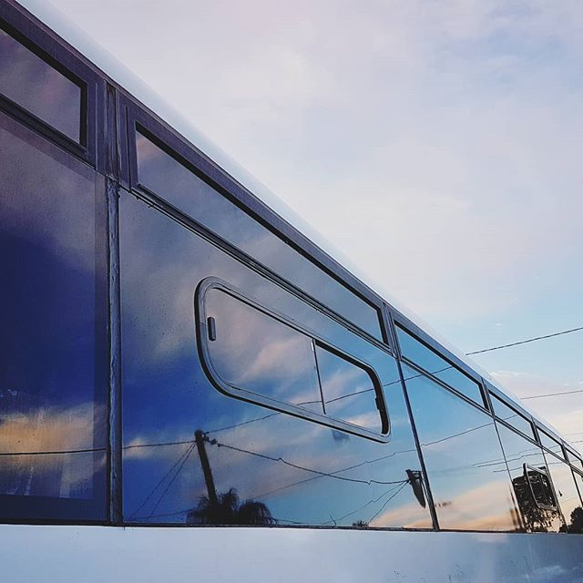 Sunset reflections and new windows on Bronte the bus. So. We are replacing a handful of fixed glass panes with 3mm aluminium composite panel (gloss black) and then cutting a hole in each panel to fit a new sliding window. We're pretty happy with the results so far! Two windows done, three to go.  #busconversion #buslife #bus #tinyhouse #skoolie #skoolieconversion #vanlife #offgrid #busbuild #rvlife #busnut #busrollwithit #livesmaller #nomad #happycamper #wander #wanderlust #homeiswhereyouparkit #ontheroad #buslifeaustralia #buslifeau
